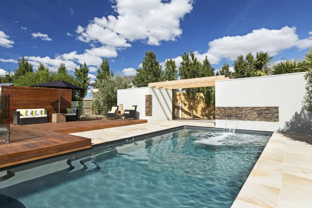 Compass Pools Australia A pool with a nice deck and water wall feature