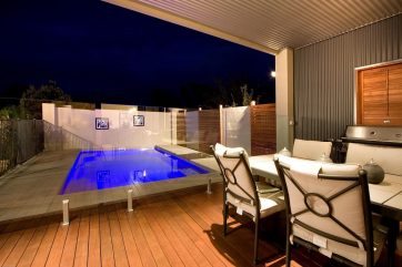 Compact X-Trainer pool with glass fencing and timber deck