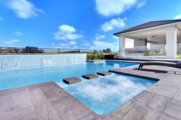 Compass Pools Australia Fibreglass pool with a spa attached and water walls