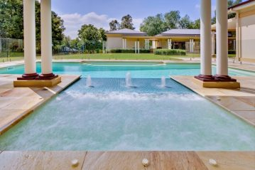 Compass Pools Australia Fibreglass pool with a sunpod water feature separating the pool and the spa