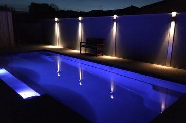 Inground swimming pool with lights on at night