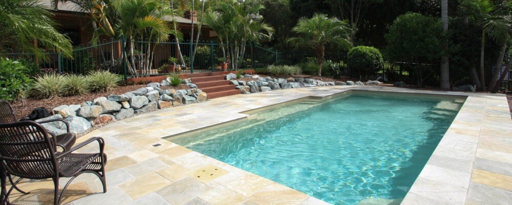 Natural pool design with stones and plants used in pool landscaping