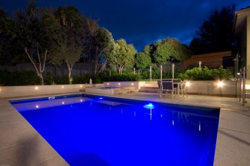 Pool and spa built partially above ground and with pool lights on