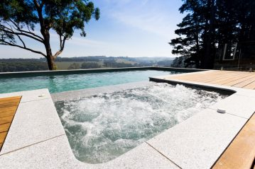 Compass Pools Australia Pool landscaping ideas Woodden deck and tiling around an infinity pool