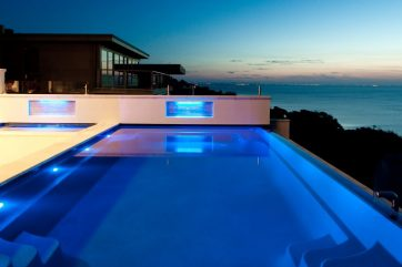 X-Trainer infinity pool with a spa and pool lights on