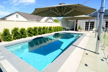 X-Trainer with tiled pool landscaping with an umbrella